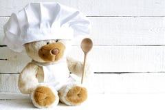 Oso de peluche en sombrero del cocinero con el fondo de la comida del extracto de la cuchara Imagen de archivo libre de regalías