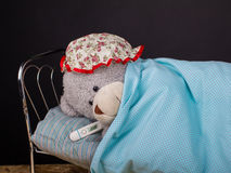 Oso de peluche en una cama con un grippe Imagen de archivo libre de regalías