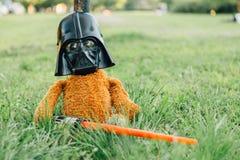 Oso de peluche en una máscara de Darth Vader con la espada Fotografía de archivo