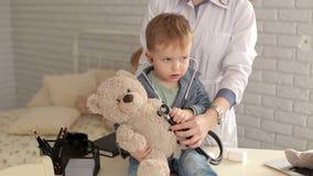 Oso de peluche de examen del paciente del doctor y del muchacho con un estetoscopio en hospital almacen de metraje de vídeo