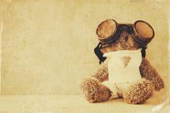 oso de peluche lindo con los vidrios experimentales en la tabla de madera Foto de archivo libre de regalías