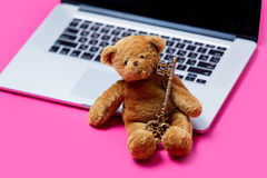 Oso de peluche lindo hermoso con llave de oro y ordenador portátil fresco en Fotos de archivo libres de regalías