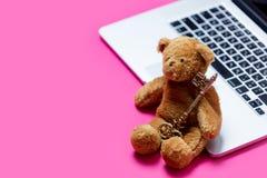 Oso de peluche lindo hermoso con llave de oro y ordenador portátil fresco en Imagen de archivo libre de regalías