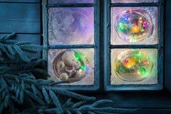 Oso de peluche magnífico en la ventana congelada para la Navidad Fotos de archivo libres de regalías