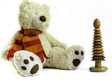 Oso de peluche mullido con la bufanda roja y el apilador de madera del anillo en el fondo blanco imágenes de archivo libres de regalías
