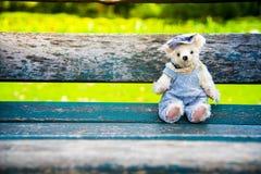 Oso de peluche que se sienta en el banco de madera Foto de archivo libre de regalías