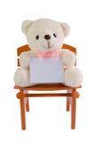 Oso de peluche que sostiene la tarjeta clara en silla marrón con el fondo blanco Imágenes de archivo libres de regalías