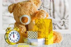 Oso de peluche, regalos y despertador en un fondo nevado Foto de archivo