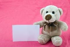 Oso del peluche con el aviso blanco en fondo rosado Foto de archivo libre de regalías