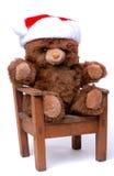 Oso del peluche con el sombrero de Santa en silla Fotos de archivo
