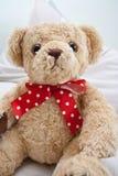Oso del peluche con la cinta roja del punto de polca Foto de archivo libre de regalías