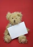 Oso del peluche con una nota en blanco Fotos de archivo