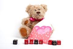 Oso del peluche que se sienta con el corazón. Día de tarjeta del día de San Valentín Fotografía de archivo