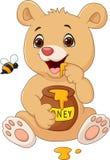 Oso divertido del bebé de la historieta que sostiene el pote de la miel aislado en el fondo blanco Fotografía de archivo