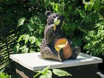 Oso feliz de la estatuilla con la miel, sentándose en una colmena Imagen de archivo libre de regalías
