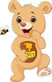 Oso lindo del bebé que sostiene el pote de la miel aislado en el fondo blanco Foto de archivo
