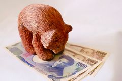 Oso que se coloca sobre los yenes de Jananese imagen de archivo libre de regalías