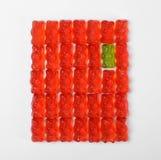 Oso verde de la jalea entre los rojos en el fondo blanco Concepto de la individualidad foto de archivo libre de regalías