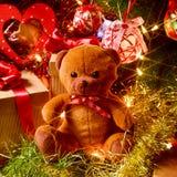 Oso y regalos de peluche debajo de un árbol de navidad Fotos de archivo libres de regalías