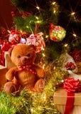 Oso y regalos de peluche debajo de un árbol de navidad Imagen de archivo libre de regalías