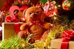 Oso y regalos de peluche debajo de un árbol de navidad Foto de archivo