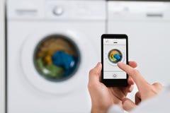 Osob ręki Z telefon komórkowy Operacyjną pralką Zdjęcia Royalty Free