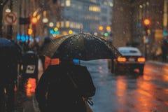 Osoba jest ubranym czer? z czarnym parasolem podczas ?nie?nego dnia fotografia stock