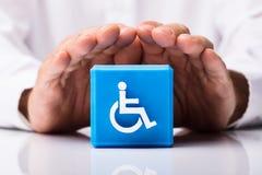 Osoba Ochrania Kubicznego blok Z Niepełnosprawną ikoną zdjęcia stock