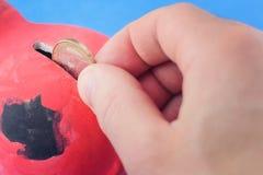 Osoba opuszcza monetę 1 euro w prosiątko banka ręka podrzuca a Zdjęcie Royalty Free