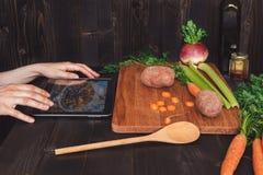 Osoba patrzeje cyfrową pastylkę i kucharstwa zdrowego jedzenie w kuchni, tnący warzywa na drewnianym stole Fotografia Royalty Free