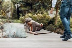 Osoba pomaga łgarskiej starszej kobiety z chodzącym kijem fotografia stock