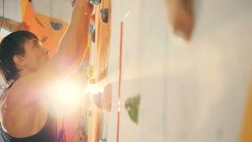 Osoba poruszająca na wspinaczkowej ścianie, boczny widok zbiory