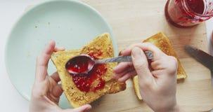 Osoba robi kanapce z masłem orzechowym i malinowym dżemem zbiory wideo