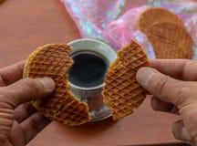 Osoba rozszczepia stroopwafel nad filiżanka kawy obrazy royalty free
