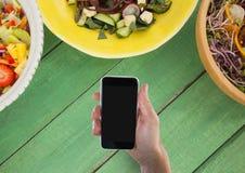 Osoba trzyma telefon przeciw zielonemu drewnianemu stołowi z jedzeniem zdjęcie stock
