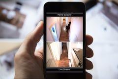 Osoba Używa Domowego system bezpieczeństwa Na telefonie komórkowym zdjęcia stock