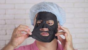 Osoba używa odmłodnieje kosmetyk maskę stawiać czoło z niechęcią i usuwa je od twarzy i rzuca je na boku zbiory wideo