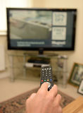 Osoba używa TV pilot do tv Zdjęcia Stock