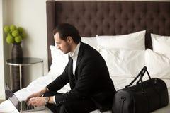 Osoba w podróży służbowej pracuje na laptopie w pokoju hotelowym zdjęcie stock