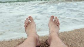 Osoba widok cieki mężczyzna relaksuje przy piaskowatą plażą z falowania morzem w tle zbiory wideo