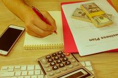 osoba wskazuje writing cele na papierze, writing plan biznesowy a Zdjęcia Stock