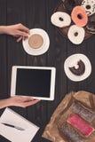 Osoba z kawą, cyfrową pastylką i donuts, Zdjęcia Royalty Free