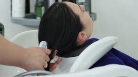 Osobista higiena, dziewczyna z długie włosy obmyciami przewodzi w zlew w piękno salonie zdjęcie wideo