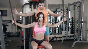 Osobistego trenera pomaga dziewczyna trenować ręki w gym Obrazy Stock