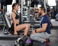 Osobistego trenera pomaga kobieta w gym zdjęcie royalty free
