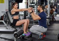 Osobistego trenera pomaga kobieta w gym zdjęcia royalty free