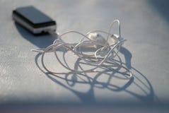 Osobisty stereo odtwarzacz mp3 kłaść na białej skórze zaświecał słońcem Artystycznego krańcowego zbliżenia makro- zamazany tło Zdjęcie Stock