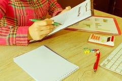 Osoby kobieta wskazuje writing cele na papierze, writing plan biznesowy przy miejscem pracy, Żeńscy mień pióra, papiery, notatki  Fotografia Stock