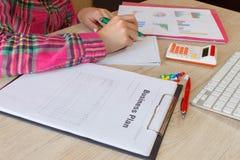 Osoby kobieta wskazuje writing cele na papierze, writing plan biznesowy przy miejscem pracy, Żeńscy mień pióra, papiery, notatki  Fotografia Royalty Free