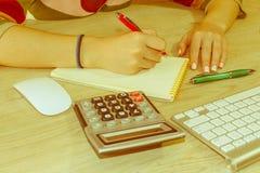 Osoby kobieta wskazuje writing cele na papierze, writing plan biznesowy przy miejscem pracy, Żeńscy mień pióra, papiery, notatki  Zdjęcie Royalty Free